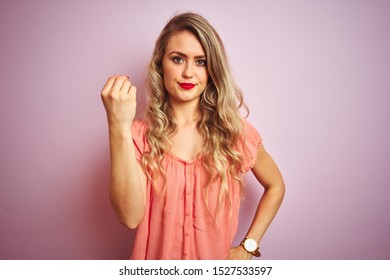 Young beautiful woman wearing t-shirt standing over pink isolated background Doing Italian gesture with hand and fingers confident expression