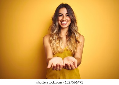 Young beautiful woman wearing t-shirt over yellow isolated background Smiling with hands palms together receiving or giving gesture. Hold and protection