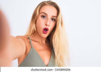Young beautiful woman wearing t-shirt make selfie by camera over isolated white background scared in shock with a surprise face, afraid and excited with fear expression