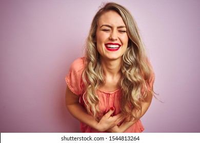 Young beautiful woman wearing t-shirt standing over pink isolated background smiling and laughing hard out loud because funny crazy joke with hands on body.