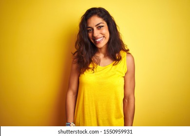 Young beautiful woman wearing t-shirt standing over isolated yellow background with a happy and cool smile on face. Lucky person.
