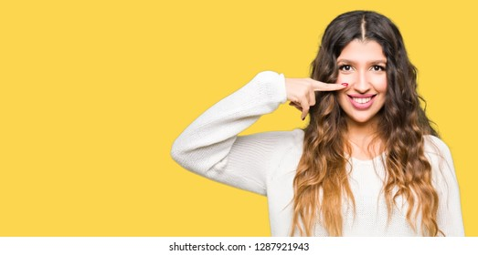 Young beautiful woman wearing white sweater Pointing with hand finger to face and nose, smiling cheerful