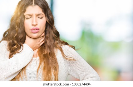 Young beautiful woman wearing white sweater Touching painful neck, sore throat for flu, clod and infection