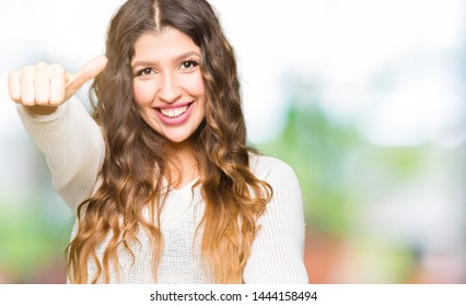 Young beautiful woman wearing white sweater approving doing positive gesture with hand, thumbs up smiling and happy for success. Looking at the camera, winner gesture.