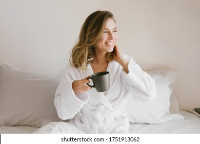 Young beautiful woman wearing white bathrobe having breakfast in bed with coffee and croissant and fresh fruits in cozy bedroom. Morning rituals.