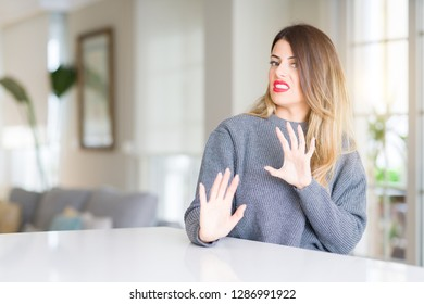 Young beautiful woman wearing winter sweater at home disgusted expression, displeased and fearful doing disgust face because aversion reaction. With hands raised. Annoying concept.