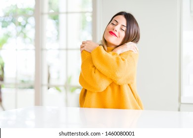 Young beautiful woman wearing winter sweater at home Hugging oneself happy and positive, smiling confident. Self love and self care