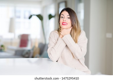 Young beautiful woman wearing winter sweater at home shouting and suffocate because painful strangle. Health problem. Asphyxiate and suicide concept.