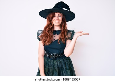 Young beautiful woman wearing witch halloween costume smiling cheerful presenting and pointing with palm of hand looking at the camera.