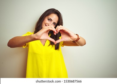 Young beautiful woman wearing yellow t-shirt standing over white isolated background smiling in love showing heart symbol and shape with hands. Romantic concept.