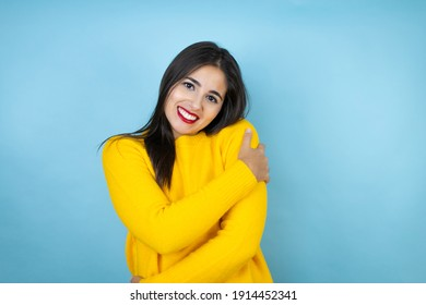 Young beautiful woman wearing yellow sweater over isolated blue background hugging oneself happy and positive, smiling confident