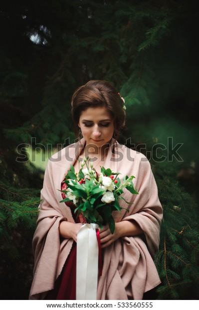 the young beautiful woman in a wedding dress with a bouquet