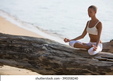 Young beautiful woman in white clothes making yoga meditation on the tree on the beach