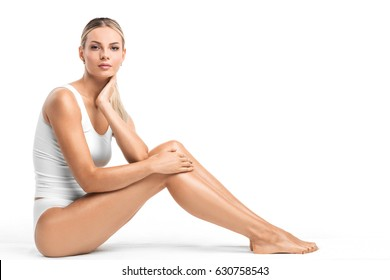 Young beautiful woman in white cotton underwear sitting isolated on white background