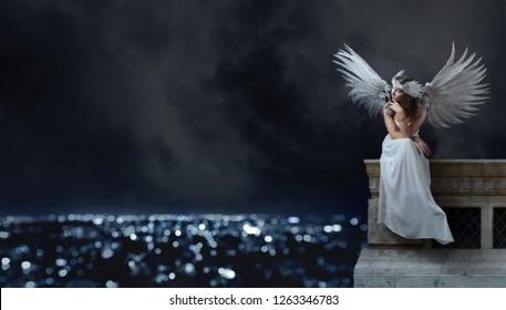 白いドレスを着た若い美しい女性で、天使の翼が屋根に座って夜の街を見ています。美しいプロの化粧、完璧な髪、自然の羽とラインストーンを持つ頭飾り