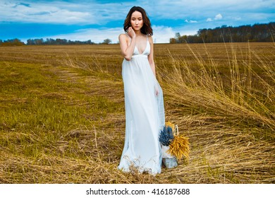 young beautiful woman in a white dress in a field of wheat