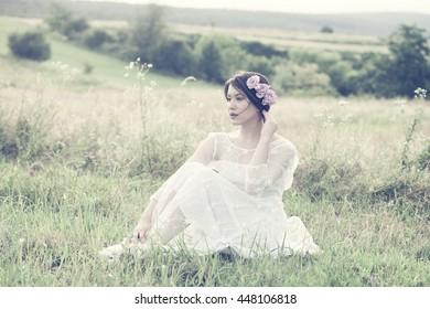 young beautiful woman in white dress hold flowers sit on grass in summer meadow