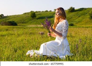 Young beautiful woman in white dress gathering flowers on the meadow