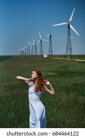 Young beautiful woman in a white dress in a field near a windmill.