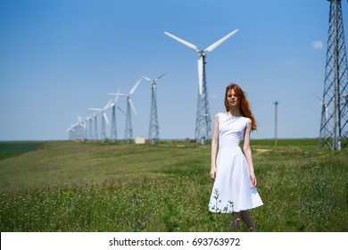 Young beautiful woman in a white summer dress in a field, wind.