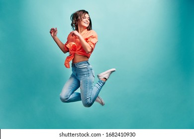 Young beautiful woman who is dressed in an orange shirt and blue jeans bouncing on a blue background with happiness and looking away and laughing. Emotion of admiration and freedom.