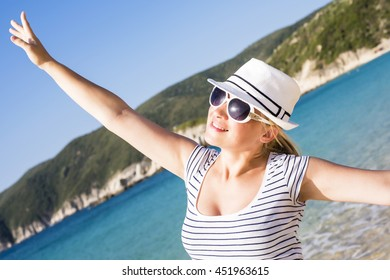 Young beautiful woman with wide open arms smiling and enjoying on the beach. Summertime concept