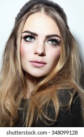 Young beautiful woman with winged eye make-up and stylish hairdo looking upwards