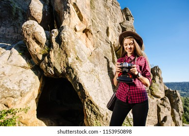 Young beautiful woman witn vintage photocamera on the rocky mountains with scenic landscape on the background