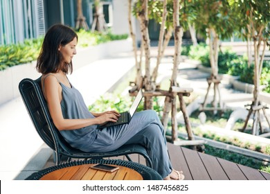 Young beautiful woman working on laptop outdoors. Freelance concept.