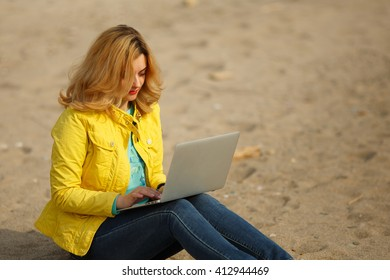 young beautiful woman working on laptop outdoors