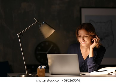 Young beautiful woman working on laptop at night