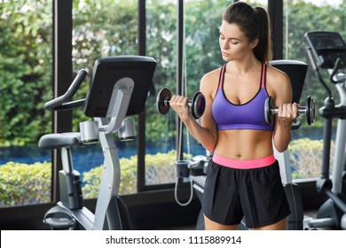 Young and beautiful woman working out with dumbbells in gym. Biceps curls.