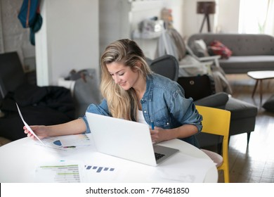 Young beautiful woman works for a computer from a home with a laptop on a white desk as a freelancer