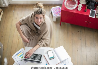 Young beautiful woman works on computer from a home with a laptop on a white desk as a freelancer.Self-employment concept. Top view