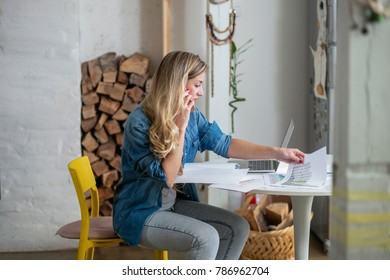 Young beautiful woman works on computer from a home with a laptop on a white desk as a freelancer