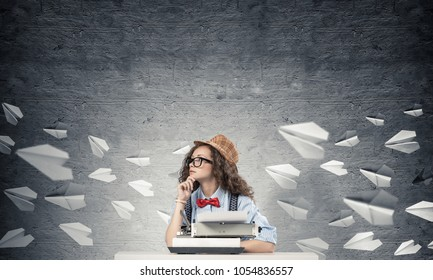 Young and beautiful woman writer in hat and eyeglasses using typing machine while sitting at the table among flying paper planes and against gray concrete wall on background.