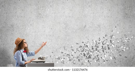 Young and beautiful woman writer in hat and eyeglasses using typing machine while sitting at the table among flying letters and against gray concrete wall on background.