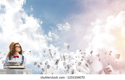 Young and beautiful woman writer in hat and eyeglasses using typing machine while sitting at the table among flying papers with cloudy skyscape on background.