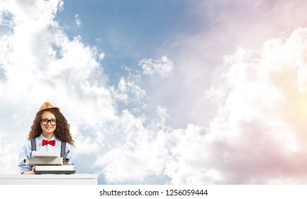 Young and beautiful woman writer in hat and eyeglasses using typing machine while sitting at the table with cloudy skyscape on background.