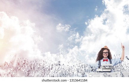 Young and beautiful woman writer in hat and eyeglasses using typing machine and pointing upside while sitting at the table among flying letters with cloudy skyscape on background.
