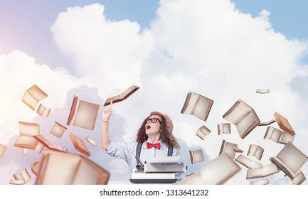 Young and beautiful woman writer in hat and eyeglasses using typing machine and pointing upside while sitting at the table among flying books with cloudy skyscape on background.