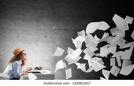 Young and beautiful woman writer in hat and eyeglasses using typing machine while sitting at the table among flying papers and against gray concrete wall on background.