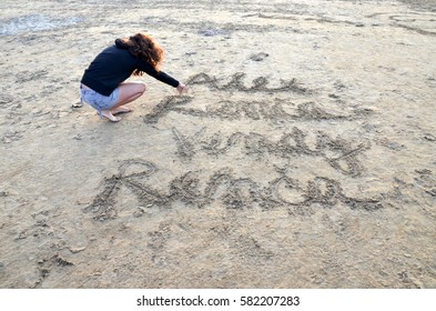 young beautiful woman writing into a sand on the beach