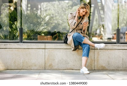 Young beautiful woman writing messages on smartphone, sitting outdoor in the city streetat sunny day. Pretty female using free wireless on cellphone. Travel and technology concept