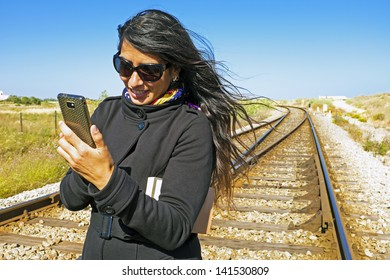 Young beautiful woman is writing a text message at a railroad track