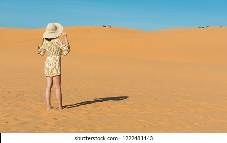 Young beautiful woman with yellow dress walking in Dubai desert sand dunes with flying fabric. Sandy dunes on sunny summer day. Back view and footsteps in the desert sand for holliday vacation concept