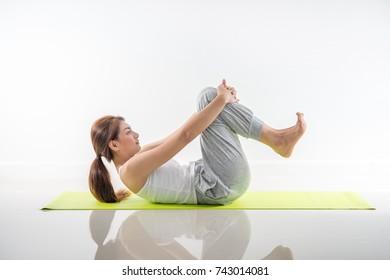 young beautiful woman yoga posing on isolated white studio background