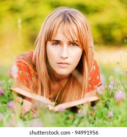 Young beautiful woman-student in red dress lies on green summer meadow with clover and reads textbook.