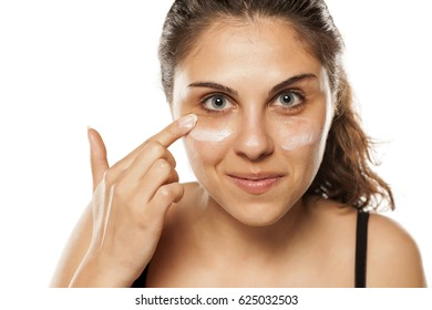 young beautiful women apply cosmetics on her face