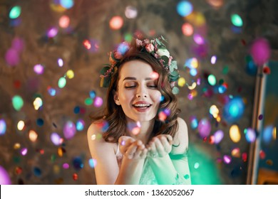Young beautiful women blowing confetti from hands. Celebration and event concept